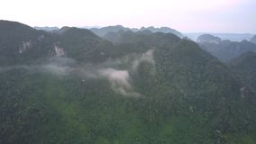 Piece of white cloud covers high green top of mountain range. With tropical forest under gray sky aerial view stock video footage
