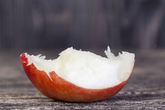 Piece of white peach. Sweet ripe bitten piece of white peach or nectarine on the wooden surface of a village table stock images