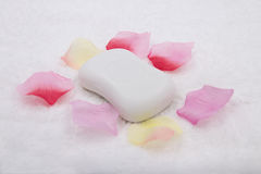 A piece of white soap. On a towel surrounded by petals Stock Images