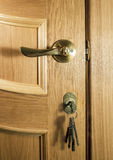 Piece of wood of an oak door with a handle and a bunch of keys Stock Photo