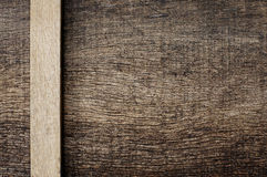 A piece of wood on the side with the old wooden. A piece of wood on the side with the old cracked wooden background Royalty Free Stock Images