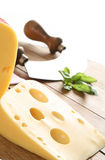 Piece of yellow cheese. On wooden table. Old chopper and some basil in background Royalty Free Stock Photos
