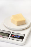 A piece of yellow cheese on a kitchen digital scale Royalty Free Stock Images