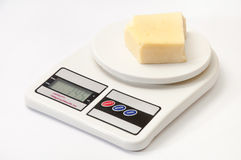 A piece of yellow cheese on a kitchen digital scale Stock Photos