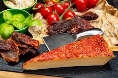 Piece of yellow hard cheese made with red sun dried tomatoes and. Herbs basil and chives stock image