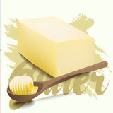 A piece of yellow milk butter with rolled slice on wooden spoon. Royalty Free Stock Photos