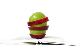 Pieces of apples and book on white Royalty Free Stock Image