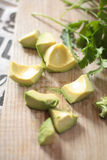 Cut avocado on wooden board. Pieces of avocado and parsley leaves on a light wooden cutting board Stock Photo