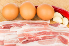 Pieces of bacon, eggs and peppers on wooden board Stock Photography