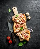 Pieces of barbecue pizza on a wooden cutting Board. On black rustic background stock images