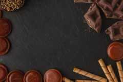 Pieces of bittersweet dark chocolate spread out on a wooden back. Ground stock image