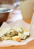 Pieces of a blue cheese on a kitchen. Some pieces of a blue cheese on a kitchen stock image