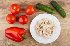 Pieces of boiled chicken meat and vegetables on wooden table Royalty Free Stock Photos