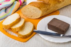 Pieces of bread on cutting board, napkin, chocolate butter, knif. Pieces of bread on cutting board, napkin, chocolate butter and knife in plate on wooden table Royalty Free Stock Image