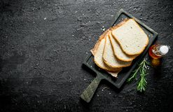 Pieces of bread on a cutting Board with rosemary and oil. On black rustic background royalty free stock image
