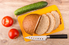 Pieces of bread on cutting board, tomatoes, cucumber and knife Stock Photography