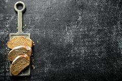 Pieces of bread with grains on the cutting Board. On dark rustic background royalty free stock photo