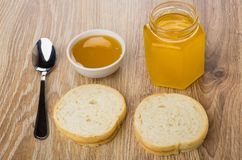 Pieces of bread, jar and bowl with honey, teaspoon. On wooden table Royalty Free Stock Photos
