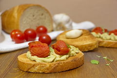 Pieces of bread with tomatoes, cream and garlic lying on the rustic table Royalty Free Stock Images