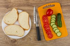 Pieces of bread, tomatoes, cucumbers on cutting board and knife Stock Photography
