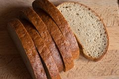 Pieces of bread on a wooden surface. Sliced rye bread on a wooden board closeup Stock Image
