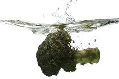 Broccoli splashing. Pieces of Broccoli falling into water Royalty Free Stock Image