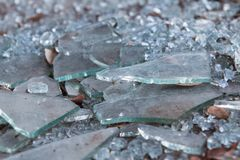 Pieces Of Broken Glass Lie On Ground At Vandalized Business. Pieces of broken glass lye on ground at building that has gone out of business Royalty Free Stock Photo