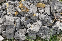 Pieces of broken slag concrete lay on the grass. Royalty Free Stock Images