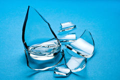 Broken Glass. Pieces of a broken water glass on a blue background royalty free stock image