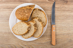 Pieces of buckwheat bread in white plate and kitchen knife Stock Photo