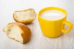 Pieces of bun, cup with milk on table royalty free stock image