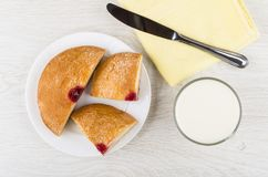 Pieces of bun with jam, knife, cup of milk, napkin. Pieces of bun with jam in plate, knife, cup of milk, napkin on wooden table. Top view stock photos