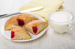 Pieces of bun with jam, knife, milk, napkin on table Royalty Free Stock Photo