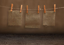 Pieces of burlap hanging on clothespins in grunge room Stock Image