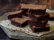 Pieces of cake chocolate brownies on wooden background. Selective focus royalty free stock photography