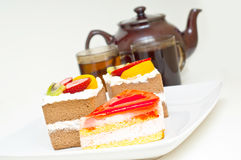 Pieces of cake, teapot and cups of tea against whi Royalty Free Stock Photography