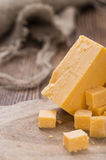Pieces of Cheddar. (detailed close-up shot) on rustic wooden background royalty free stock image
