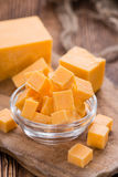 Pieces of Cheddar. (detailed close-up shot) on rustic wooden background royalty free stock photos