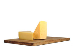 Pieces of cheese on a board. Pieces of cheese on a bamboo chopping board Stock Photos