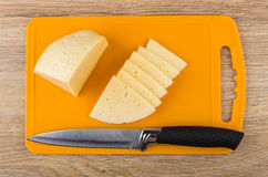 Pieces of cheese on plastic cutting board and knife Royalty Free Stock Image