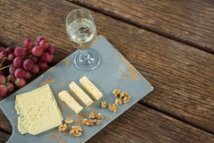 Pieces of cheese, walnut, grapes and glass of wine on tray. Over wooden table Royalty Free Stock Photography