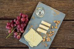Pieces of cheese, walnut, grapes and glass of wine on tray. Over wooden table Stock Photos