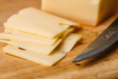 Pieces of cheese on wooden cutting board and knife Royalty Free Stock Image