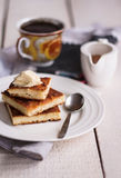 Pieces cheesecake  and a cream, a spoon, pour honey, coffee. On the white wooden boards Stock Photo