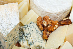 Pieces of cheeses on wooden plate Stock Images