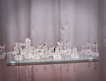 Pieces on the chessboard. Set of chess figures on the playing board .Glass Chess Stock Images