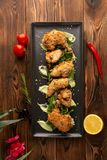 Pieces of chicken in batter on a black plate on a wooden background stock photo