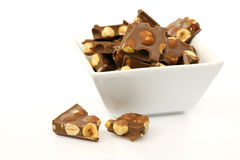 Pieces of chocolate. Filled with hazelnuts in a white bowl Royalty Free Stock Image