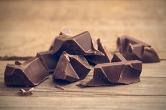 Pieces of chocolate bar on wooden background, toned Royalty Free Stock Photography