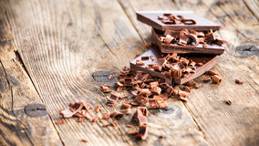 Pieces of chocolate bow wooden board. Royalty Free Stock Photo